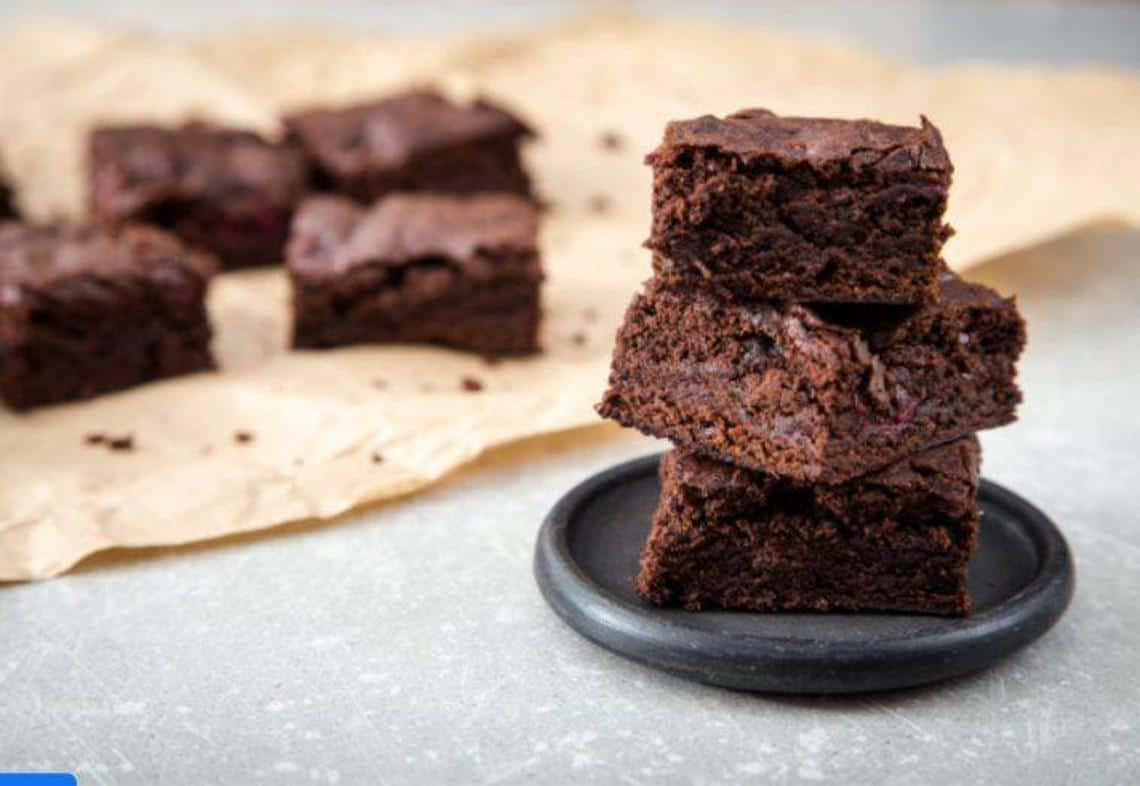 coconut flour brownies stacked on a plate with more on a parchment paper in the background