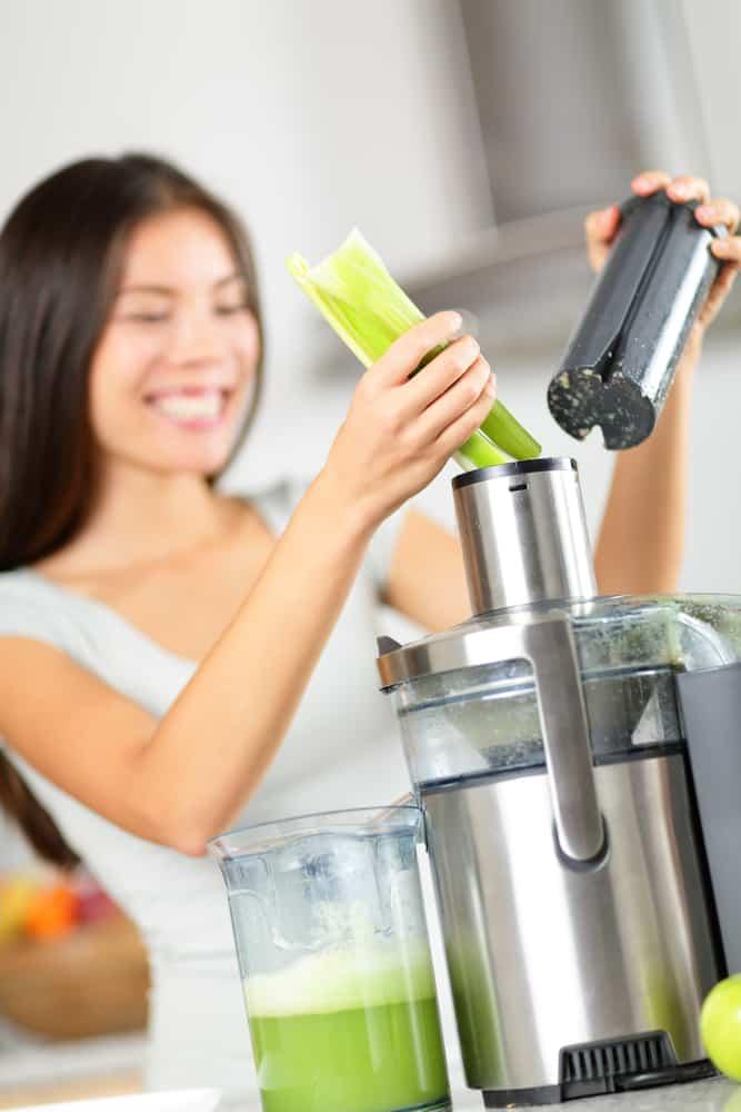 Woman putting celery into a juicer to make fresh celery juice.