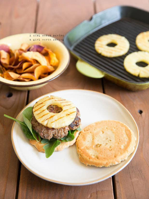 A Hawaiian burger on a plate with grilled pineapple on the background