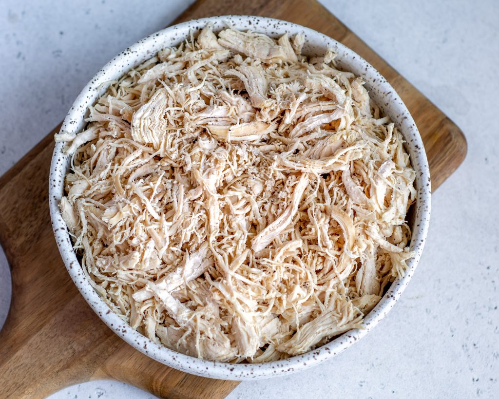 chicken cooked in an instant pot that has been shredded and is placed in a white bowl