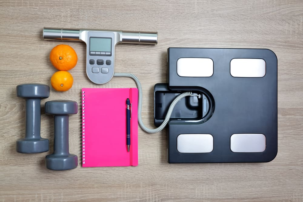BMI Scale with notebook, free hand weights and two oranges on the ground.