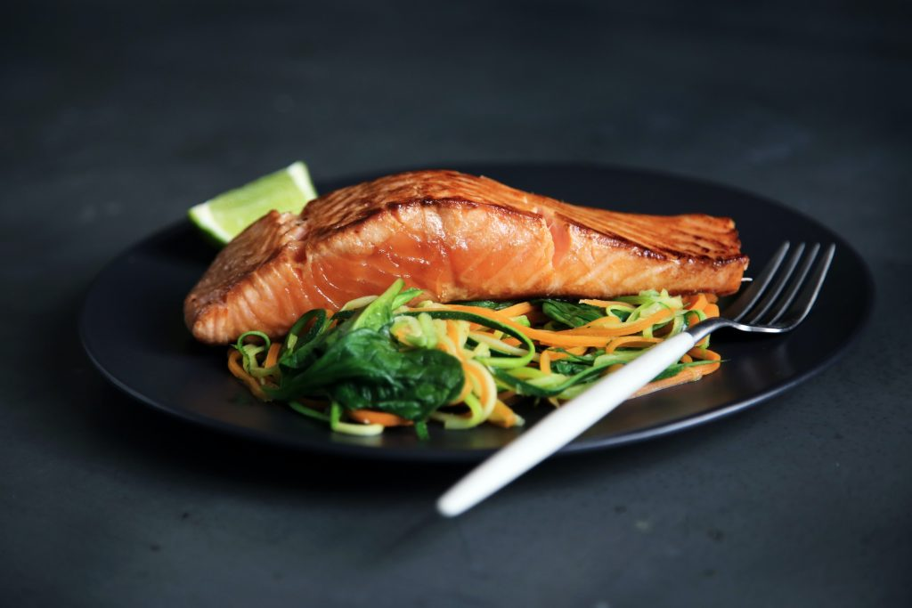 Baked salmon on top of vegetable noodles on a black plate
