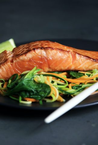 Baked salmon on top of vegetables noodles on a black plate