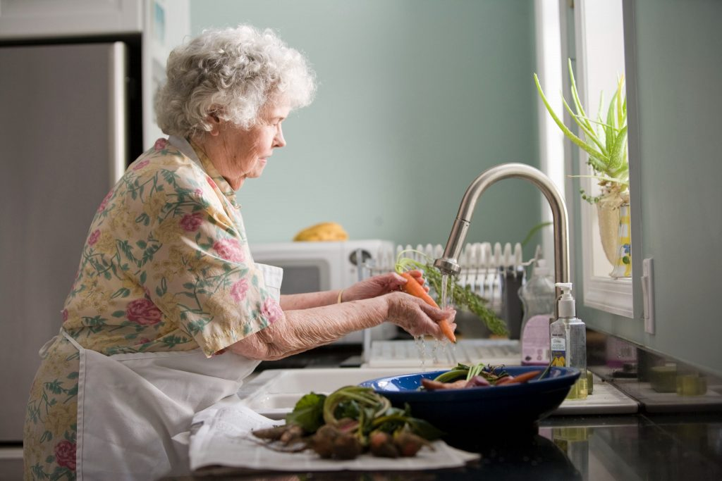 Older woman cleaning vegetables in the sink preparing them for dinner.
