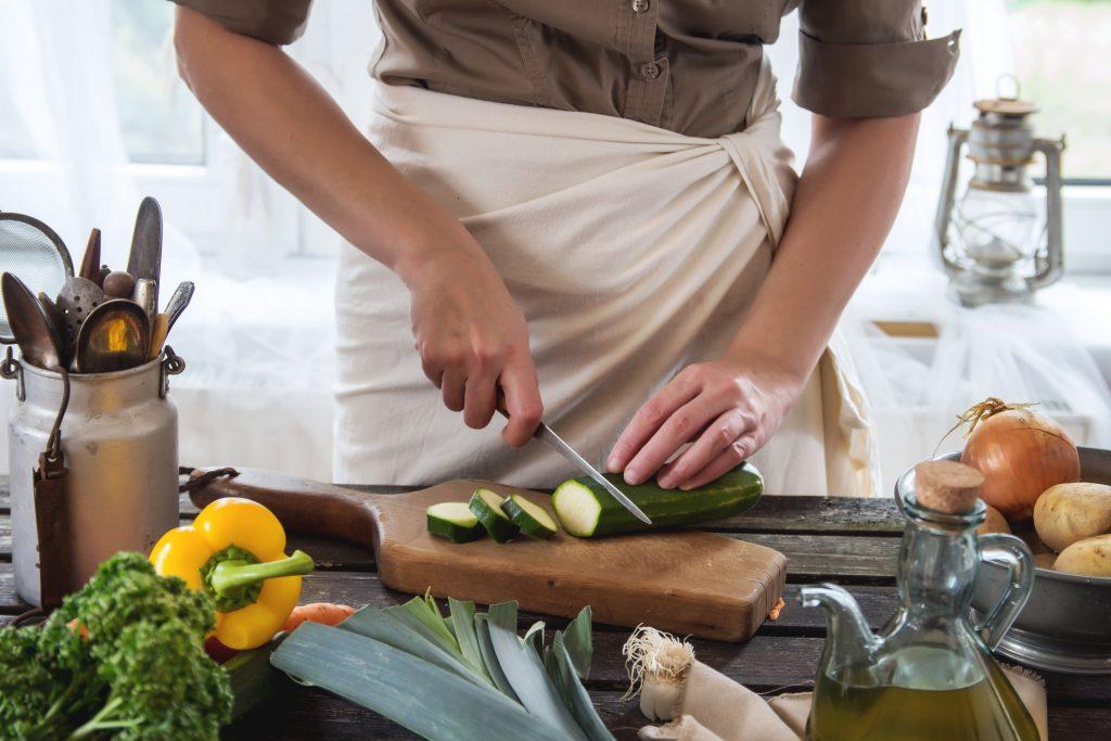 woman cutting zucchini in a kitchen