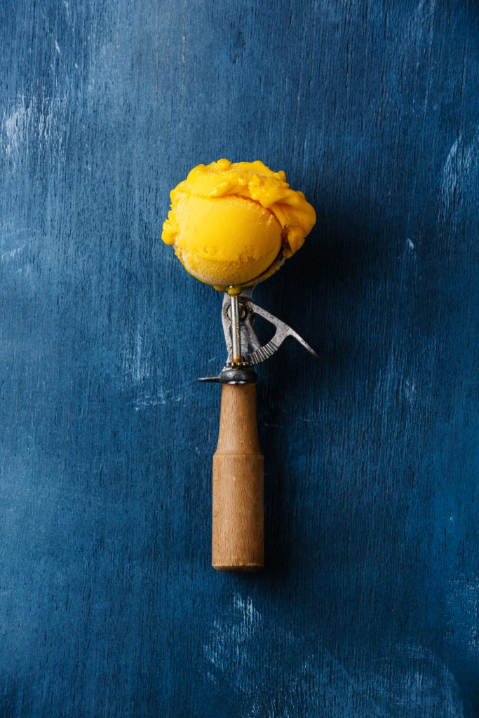 A ice cream scooper filled with a scoop of mango ice cream on a blue background