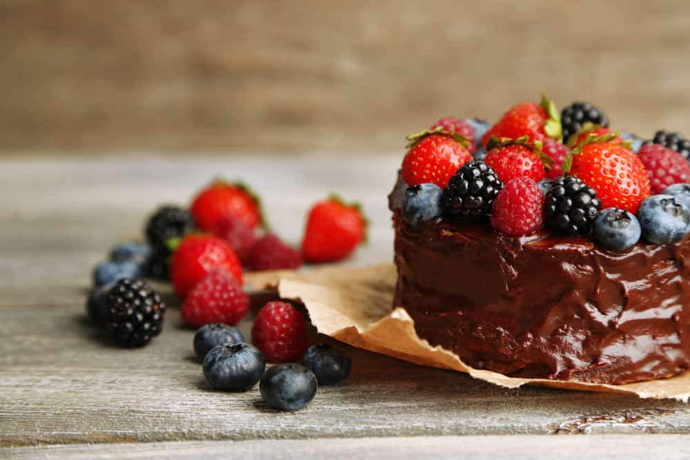 Tasty paleo chocolate cake with different berries on wooden table