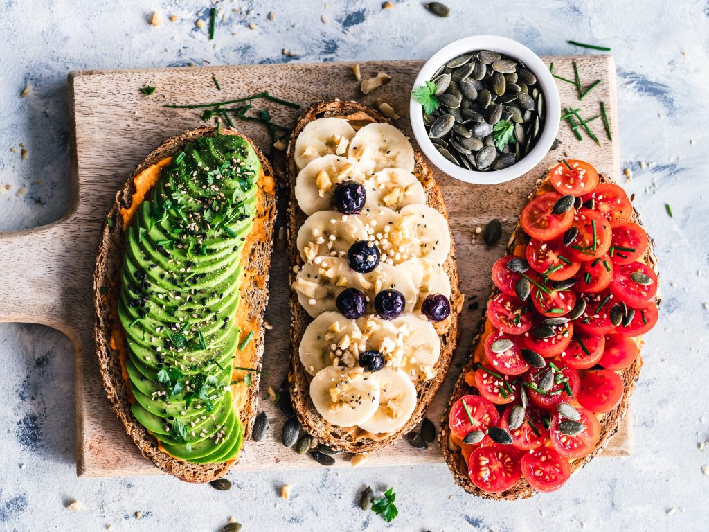 Three slices of toast. One is topped wsith avocdao slices, one is stopped with bananas and one is topped with sliced tomatoes.
