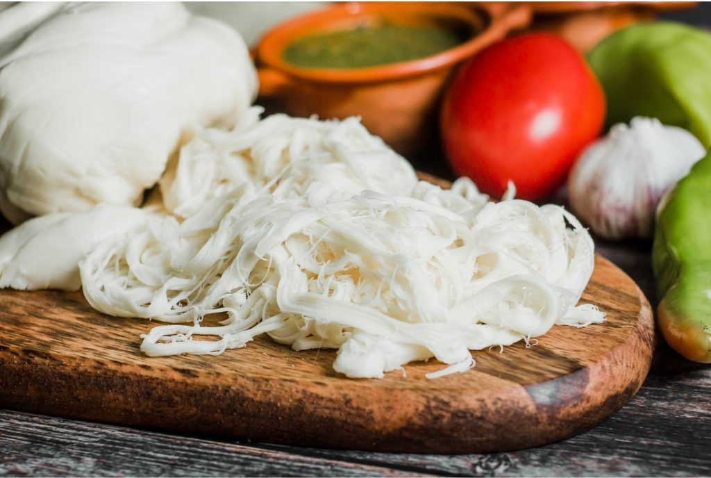 Freshly made Oaxaca cheese on a cutting board with balls of cheese.