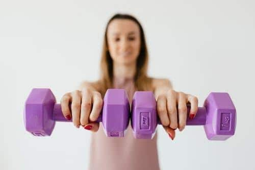 young woman lifting hand weights