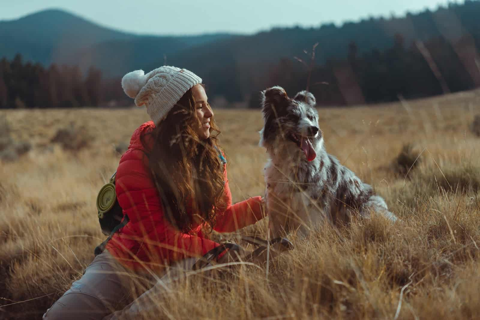 woman sitting in field with dog