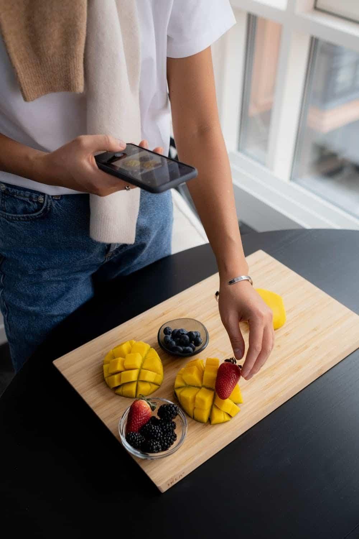 woman taking photo of mango on cutting board