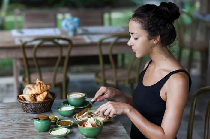 Young woman having breakfast and cut pankaces with golden fork and knife