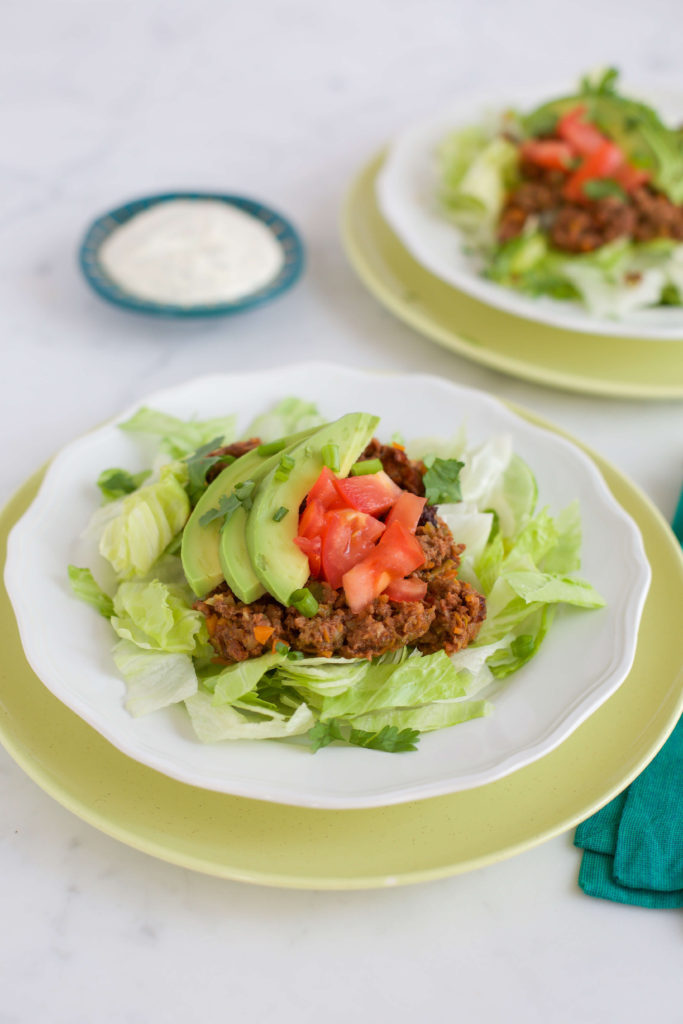 slow cooker taco meat on a platte with lettuce and tomatoes