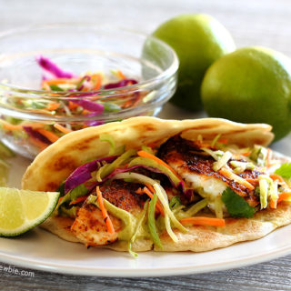 A Mexican dish of Spicy Tilapia Baja Tacos with Lime Slaw and Avocado Cilantro Sauce