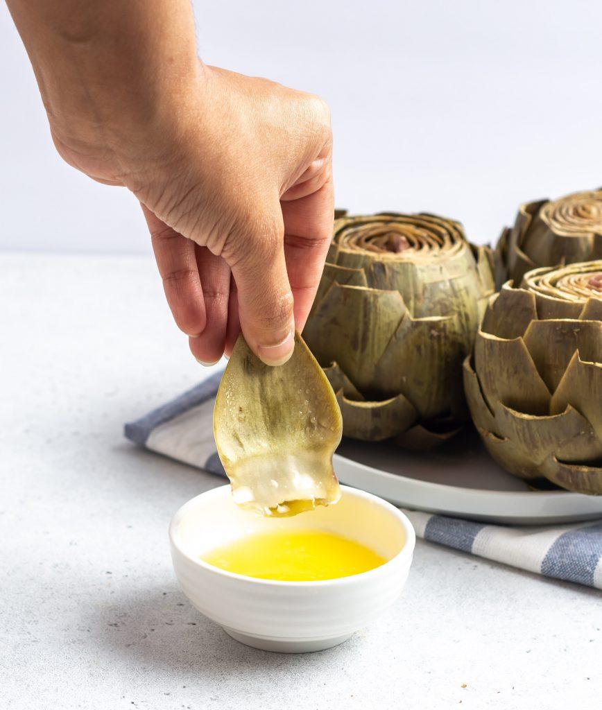 dipping an instant pot artichoke in garlic butter