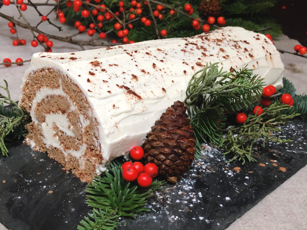 gingerbread cake roll on a plate with pine cones and pine leaves