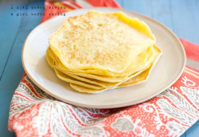 Paleo tortillas stacked on a plate on a table cloth