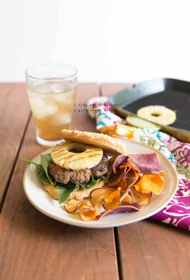 Hawaiian burgers on a plate with grilled pineapple in the background